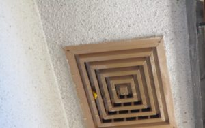 スズメバチの巣が取れないので燻蒸剤(黄色)を換気口の隙間から差し込みを行う